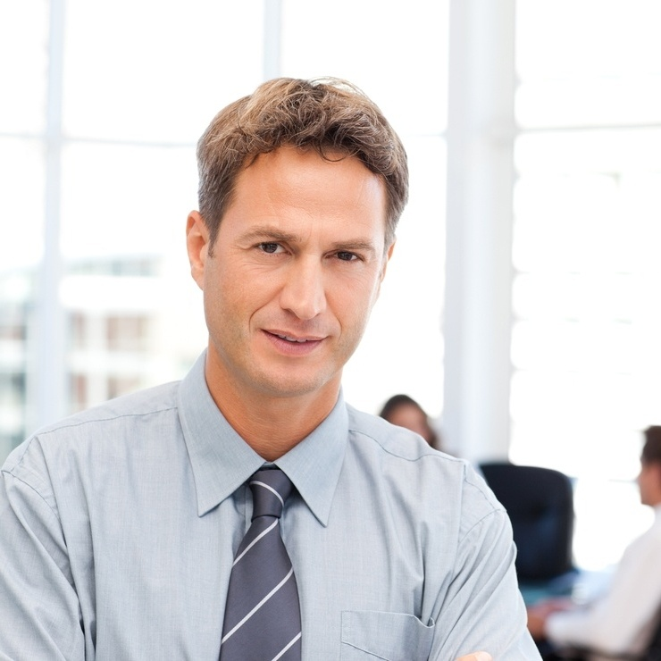 Severe businessman standing in front of his team while working at a table in the background-717308-edited.jpeg
